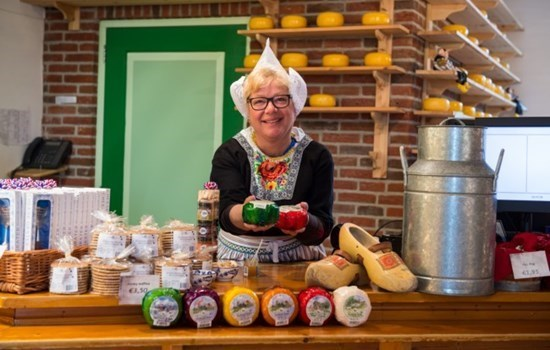 Woman in traditional clothing offering cheese in a cheese farm in Amsterdam, the Netherlands/Holland